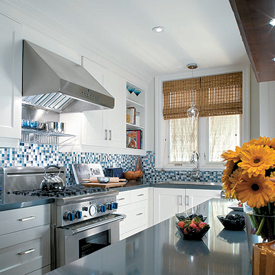 Crisp white kitchen cabinets with beachy blue glass tile backsplash, stainless steel appliances and bamboo roman shades
