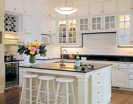 Crisp white kitchen cabinets with glass front doors and shiny black granite countertops counter tops! White counter bar stools, stainless steel appliances and subway tiles! white black kitchen colors