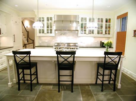 Stone slate tiles floors, glass front white kitchen cabinets, white carrara marble subway tiles backsplash countertops, black x-back counter stools counterstools, glass pendant island lights, white kitchen island and soft yellow paint color walls, blue green gray white yellow kitchen colors