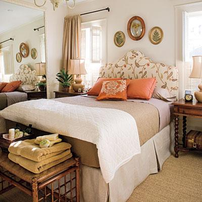 fashionista06: bedrooms - upholstered headboard orange persimmon pillows antique nightstands mirror  Warm bedroom  Floral headboard, orange pillows, linen bed