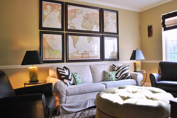 media rooms - Benjamin Moore Quincy Tan - slipcovered sofa zebra green geometric pillow round tufted ottoman lamps world map art leather club chairs roman shade chair rail