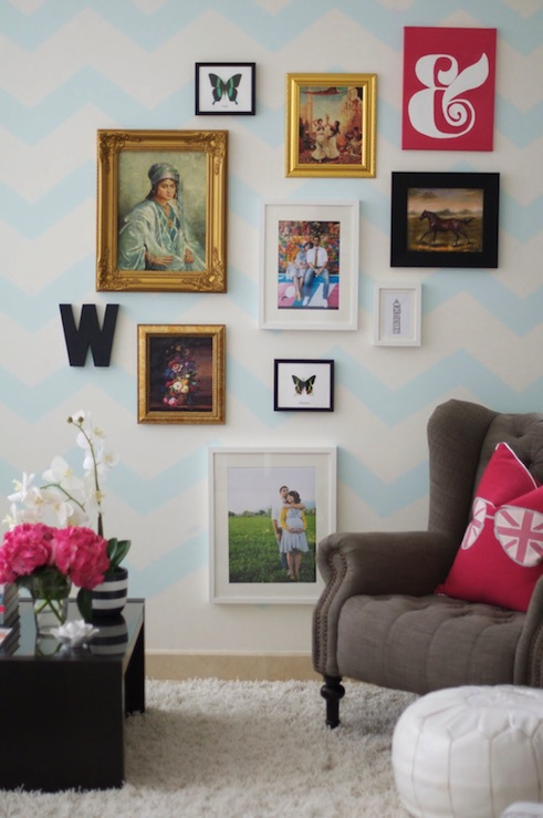 living rooms - chevron painted wall mixed media photo gallery wall Windsor Smith Riad fabric pillows tufted grey wingback chair gold frames wall letter framed butterfly potted orchid