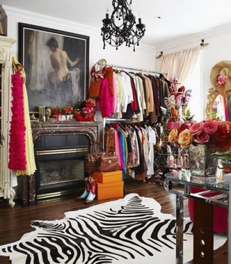 Gina Kates: closet  white & black zebra cowhide rug, fireplace, drapes and black crystal chandelier.