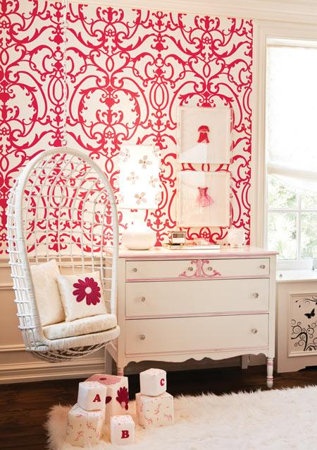 nurseries - Rattan Hanging Chair red wallpaper white dresser pink accents glass knobs glider white flower pillows white flokati rug toy blocks white gourd lamp pink red dress white gallery frames white roman shades adorable chic