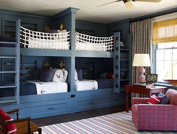 boy's rooms - blue double bunk beds white fish net white blue nautical bedding small porthole mirrors ivory blue striped rug red table lilac lamp red blue club chair bamboo roman shades gray curtains drapes beadboard ceiling ceiling fan