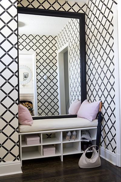 Suzie: entrances/foyers - black beveled floor mirror shoe rack bench white cushion pink lumbar pillows black white lattice wallpaper wood floors pink boxes umbrella white black pink entrance foyer