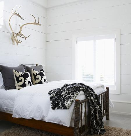 bedrooms - white walls planks white black pillows gray silk pillows rustic bed  Michael Graydon Photography.   white gray black bedroom design