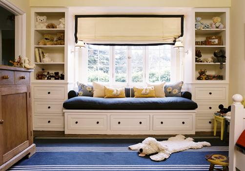 boy's rooms - ivory roman shade black ribbon trim blue bench cushion built-ins window seat cabinets shelves blue striped rug yellow walls paint color blue boy's playroom