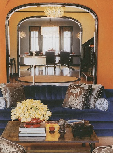living rooms - blue sofa orange walls brown pillows  Living Room Inspiration  Orange walls paint color, blue velvet tufted sofa and gray pillows.