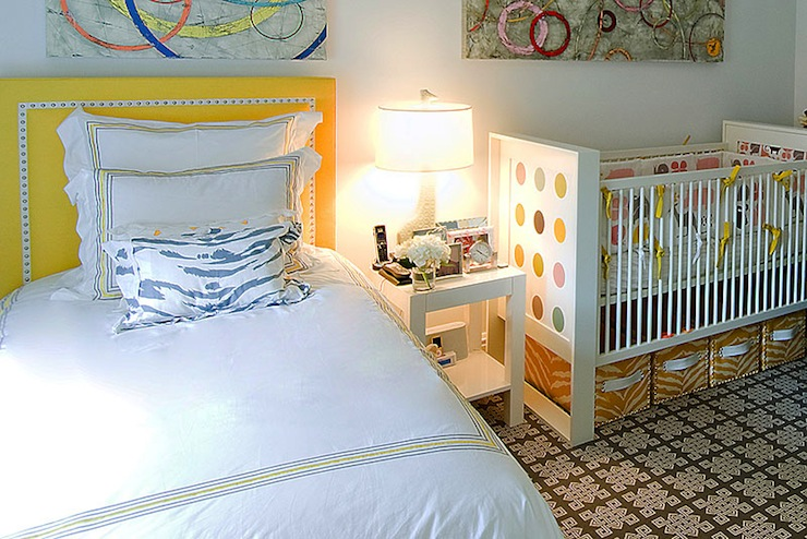 nurseries - Jonathan Adler Giraffe Lamp yellow nailhead trim headboard white bedding yellow gray border white blue zebra pillow white nightstand white modern crib cloth white yellow zebra storage bins brown rug abstract art