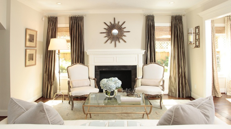 living rooms - gray beige greige walls taupe silk drapes bronze sunburst mirror white gray bergere chairs brass glass coffee table floor lamp black marble fireplace