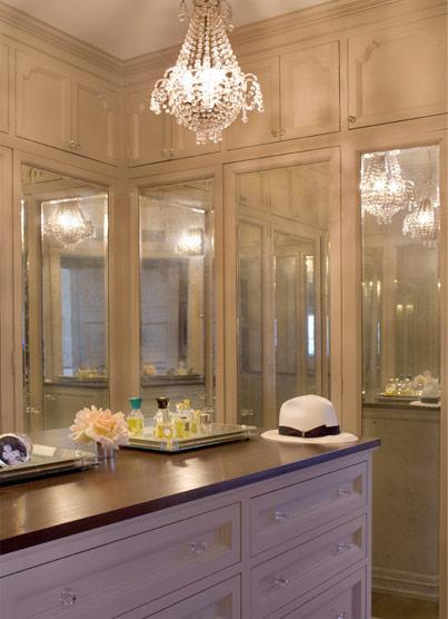 closets - chic walk-in closet white cabinets mirrored doors crystal chandelier island  Kristen Buckingham  chic walk-in closet design with crystal