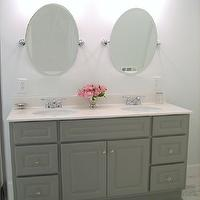 Ten June - bathrooms - Martha Stewart - Cement Gray - gray bathroom vanity, double vanity, gray double vanity, master bathroom, dual sinks, his and hers sink, crystal hardware, light countertops, light counters, oval mirrors, oval vanity mirrors, pivoting bathroom mirror, pivoting oval bathroom mirror, pivoting oval vanity mirror, marble tiled floors, marble floor tile, gray walls, gray bathroom walls, gray wall color, polished nickel bathroom sconces, polished nickel and white glass sconces, frosted glass sconce, cement gray, gray bathroom vanity, painted bathroom vanity, painted cabinets, painted bathroom cabinets, cream countertops, gray paint, gray paint colors, gray bathroom paint colors,