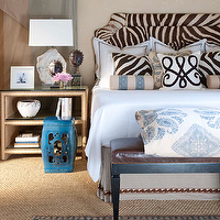 Ceylon et Cie - bedrooms: zebra print headboard, zebra hide headboard, hide headboard, zebra hide upholstered headboard, zebra print pillows, blue striped bolster pillows, brown and white scroll print pillows, box pleated bed skirt, bed skirt, linen box pleated bed skirt, bed skirt with tape trim, white bedding, white bed linens, brown leather bench, brown leather upholstered bench, blue and white blockprint bedding, blue and white block print duvet cover, sisal carpet, natural fiber carpet, blue and gold rug, marble lamp, marble table lamp, sculptural heads, photo frame, rafia wrapped nightstand, two shelf rafia wrapped nightstand, rafia wrapped nightstand with nailhead trim, blue garden stool, cafe au lait wall color, zebra headboard, cowhide headboard, zebra cowhide headboard, fabric wrapped tables, raffia tables,