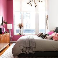Marcus Hay - bedrooms - pink accent wall, bright pink accent wall, hardwood floors, zebra print rug, white and gray zebra print rug, gray duvet cover, chunky gray throw, gray tasseled throw, pink pillows, pink embroidered pillows, gray pillows, black and white pillows, modern accent table, tall gray lamp, modern gray lamp, mid-century dresser, mid-century modern dresser, window blinds, light diffusing window blinds, pink and gray bedroom, Satellite Chandelier, Safari Rug, gray zebra rug, pink and gray bedroom,