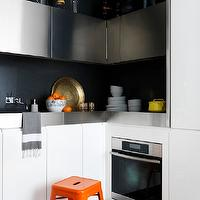 Marcus Hay - kitchens - small kitchen, modern kitchen, compact kitchen, modern white kitchen cabinets, modern white cabinets, modern white cabinetry, stainless steel kitchen cabinets, stainless steel counters, stainless steel countertops, hardwood floors, l-shaped kitchen, compact l-shaped kitchen, bright orange step stool, orange step stool, black backsplash, built-in single oven, stainless steel single oven, blue and white chevron rug, small modern kitchen, orange tolix stool, stainless steel cabinets, stainless steel kitchen cabinets,